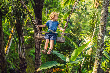 A boy on a swing over the jungle, Bali