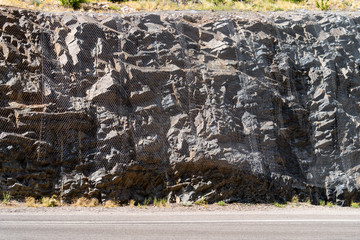 A net placed over rocks along the side of a mountain road prevents a rock slide from damaging the road, cars and pedestrians