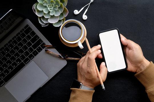 Man using mobile smartphone on dark home business desk.