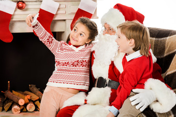 happy kids taking selfie with santa while sitting in armchair together