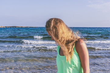 A woman with her hair loose in the wind is out of focus on the background of the sea