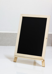 blank slate blackboard on white floor background, copy space.