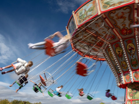 The motion of people on a fairground ride on a summer's day
