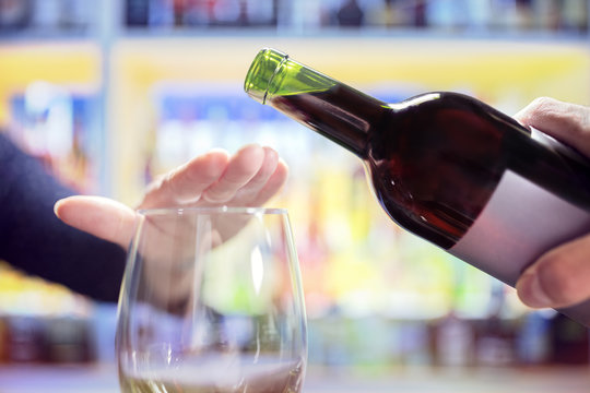 Woman hand rejecting more alcohol from wine bottle in bar
