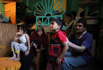 Married couple Heba Mahmoud and Samri Ragab, who are both visually impaired, sit with their children in the living room of their home in Cairo