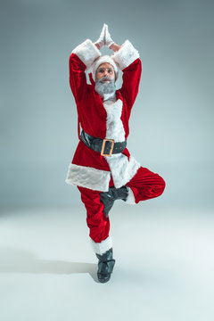 Funny serious guy with christmas hat sitting at yoga pose at studio. New Year Holiday. Christmas, x-mas, winter, gifts concept. Man wearing Santa Claus costume on gray. Copy space. Winter sales.