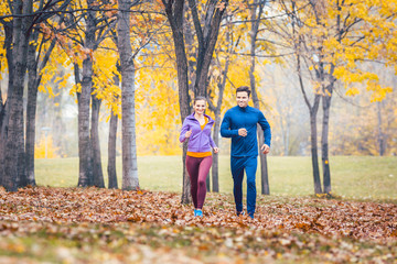 Man and woman running as fitness sport in an autumn park with colorful foliage