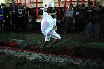 Shi'ite muslim walks on hot coals at a ceremony during the Ashura festival at a mosque in central Yangon