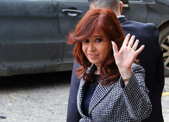 Former Argentine President Fernandez de Kirchner waves as she leaves the Federal Justice building in Buenos Aires