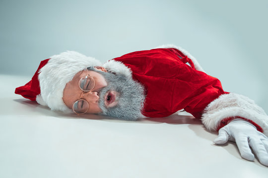 The tired Santa Claus lying on floor on white studio background. Man wearing Santa Claus costume on gray. Copy space. Winter sales.