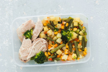Delicious and healthy lunch. Chicken meat with boiled vegetables in container on grey background,
