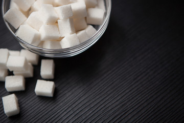 White sugar cubes on black table with copy space, can be used as food background