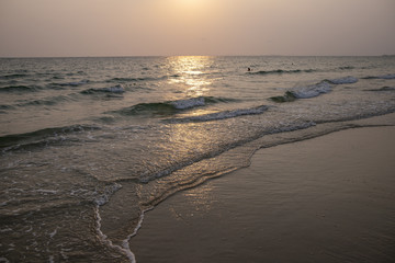 Orange sunset landscape with wavy sea and beach sand. Sunset by the sea. Romantic evening seascape with sunset