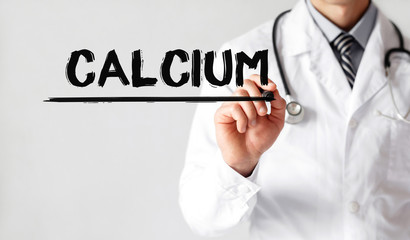 Doctor writing word CALCIUM with marker, Medical concept