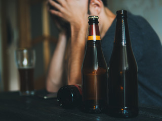 A man addicted to alcohol. Hold hands on the head, the concept of loneliness