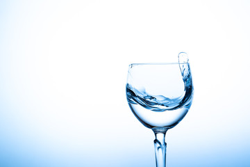 Water splashing in the luxury wine glass close up.  Concept of good healthy and refreshment.  Copy space on left side on the image.