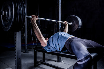 Athletic Man In Gym Exercising On The Barbell Bench Press.