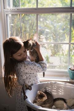 A girl holding kittens.