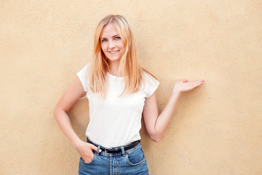 Hipster girl wearing blank white t-shirt and jeans posing against rough street wall, minimalist urban clothing style, woman shows by hand