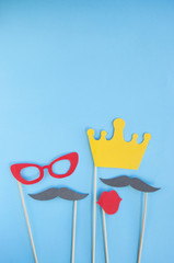 Colorful photo booth props glasses, lips, crown and moustaches on blue background with copyspace. Set of party props.