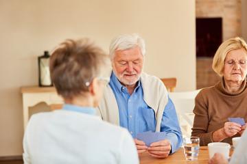 Drei Senioren spielen zusammen Karten