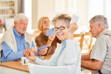 Ehrgeizige Senior Frau beim Karten spielen