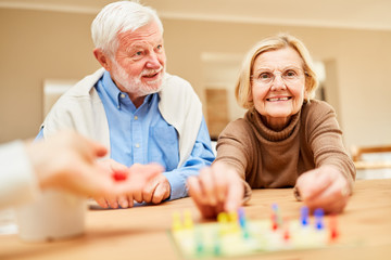 Senioren Paar spielt mit Freunden ein Brettspiel