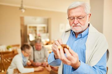 Senior Rentner Mann spielt mit einem Holzpuzzle