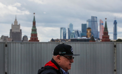 A man wearing a cap with the Mercedes-Benz logo walks across the Great Moskvoretsky Bridge in central Moscow