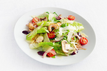 romaine salad with prawns, champingons, tomatoes, olives, and onion dressed with modena vinegar and olive oil and sprinkled with parmesan