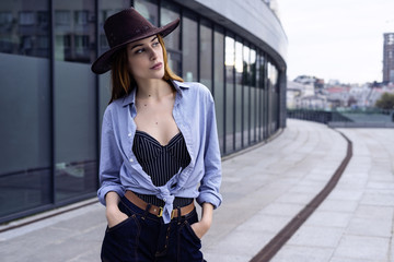 Outdoor fashion portrait of glamour sensual young stylish lady wearing trendy fall outfit , brown hat , blue shirt and blue jeans