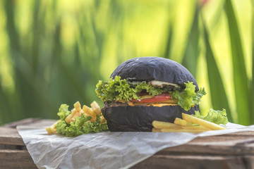Burger made with black charcoal bun served with potato wedges, lettuce and sauce on wooden rustic table