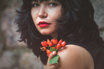 Sexy beautiful pretty brunette with red lipstick with red rose hips in hand