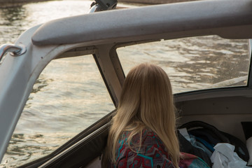 Woman with fluttering hair sails on tour boat on river, enjoys a beautiful view of the city at sunset.