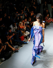 Models present creations at the On|Off catwalk show during London Fashion Week in London