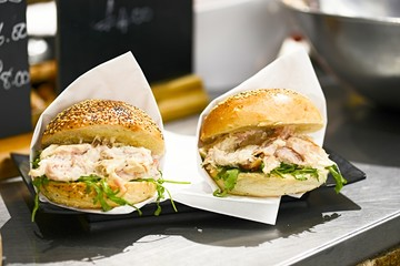Tasty appetizing burgers with meat, cheese and vegetables at outdoor food festival