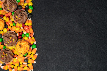 Halloween themed candy and treats - candy corn and cupcakes. Right aligned, black background