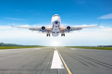 Passenger airplane landing at in good clear weather with a blue sky clouds on a runway. Wall mural