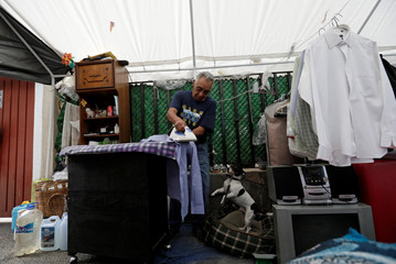 Enrique Alcantara irons shirts in his tent near the site where his building was damaged by the devastating earthquake, that took place in Mexico City last year