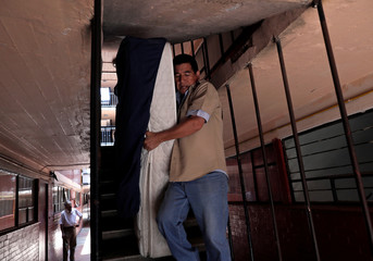 Residents remove a mattress outside their apartment where a building was damaged by the devastating earthquake, that took place in Mexico City last year in the Tlalpan neighbourhood