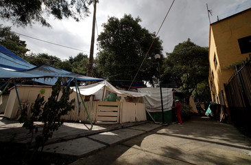 Maria Guadalupe Padilla is pictured outside her tent in the Tlalpan neighbourhood, near the site where her building was damaged by the devastating earthquake, that took place in Mexico City last year