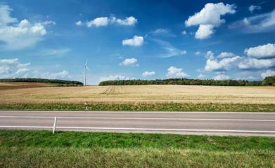 Landstraße seitlich vor Landschaft mit Windkraft im Sommer Saarland bei Merzig