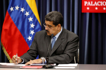Venezuela's President Nicolas Maduro signs a document during a news conference at Miraflores Palace in Caracas