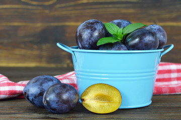 Plums in the bowl wooden background