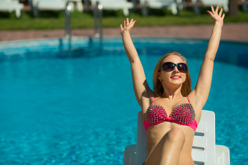 beautiful young girl with a slender figure sunbathing near the pool in summer
