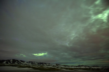The northern lights pierce the clouds