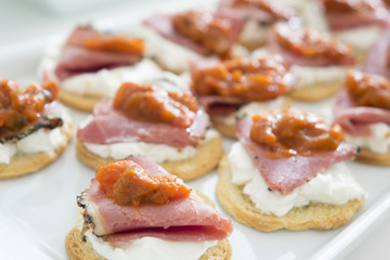 Canape with smoked meat, cheese and tomato sauce