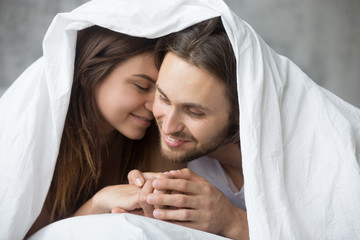 Tender romantic couple wake up having intimate moment relaxing under blanket in bedroom, loving girlfriend kissing boyfriend  whispering enjoying good relationship, lovers spend morning in bed