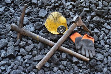 Lighted vigil light candle with the miner belongings (helmet, gloves, pickaxe, vest, belt)