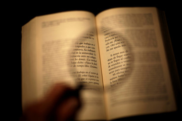 A man places a loupe over a book at his house in Ciudad Juarez